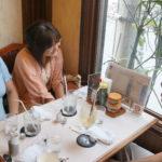 カフェでライターと談笑するYOSCA執行役員の阿部